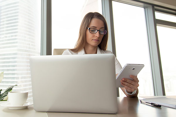 Woman at computer on mobile phone